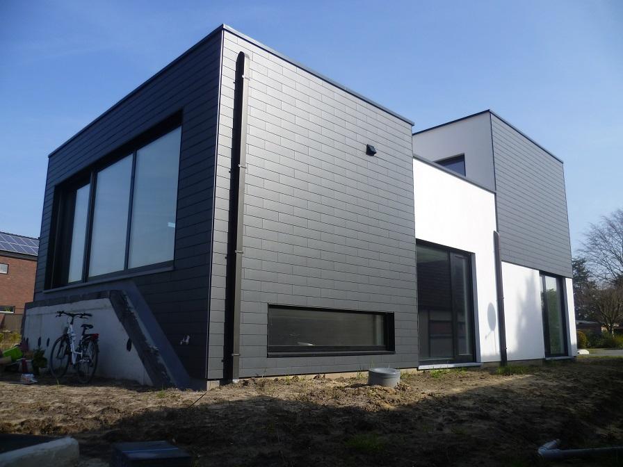 Achtergevel van moderne nieuwbouwwoning in leien en pleister te Stokrooie. Een realisatie van creja architectuur.