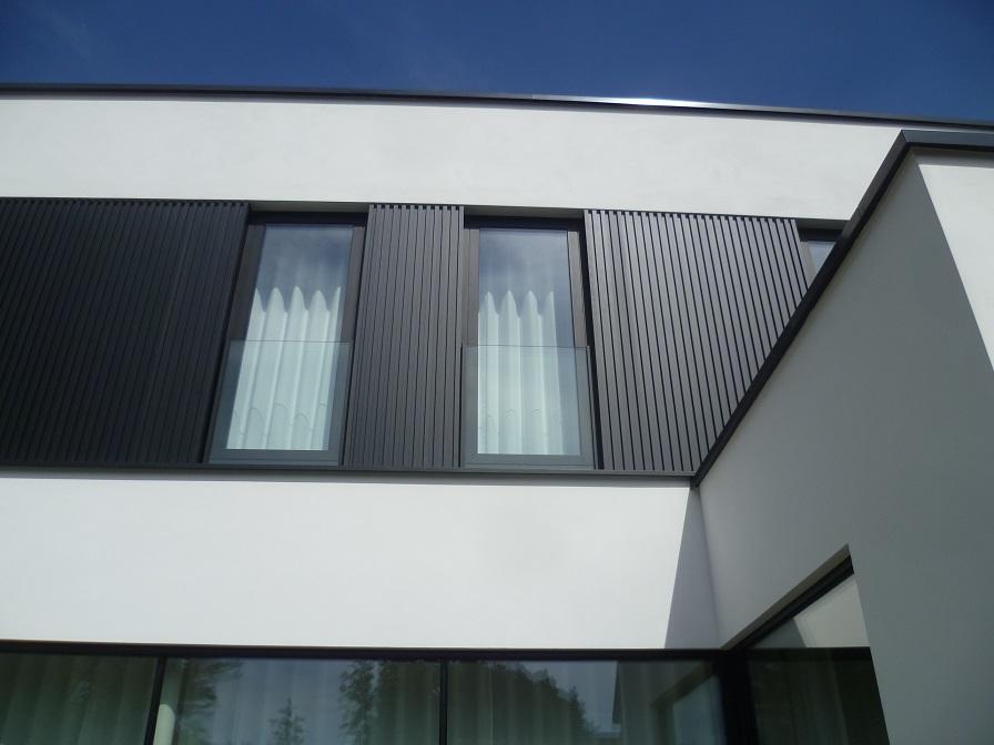 Detailfoto combinatie witte pleister en donkere aluminium gevelbekleding. Een ontwerp van creja architectuur.